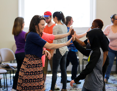 Festival goers practice self defense techniques with each other.