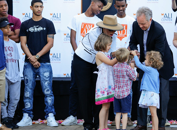 Lonnie Ali (left) and Mayor Greg Fischer (right) open a box of butterflies to release with a group of children.