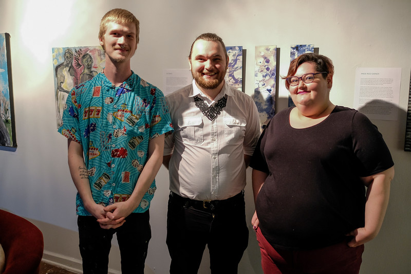 (From left to right) Curators of the Queer Voices art exhibit John Faughender, Kevin Warth, and S.N. Parks pose for a group photo in front of some of the art work.