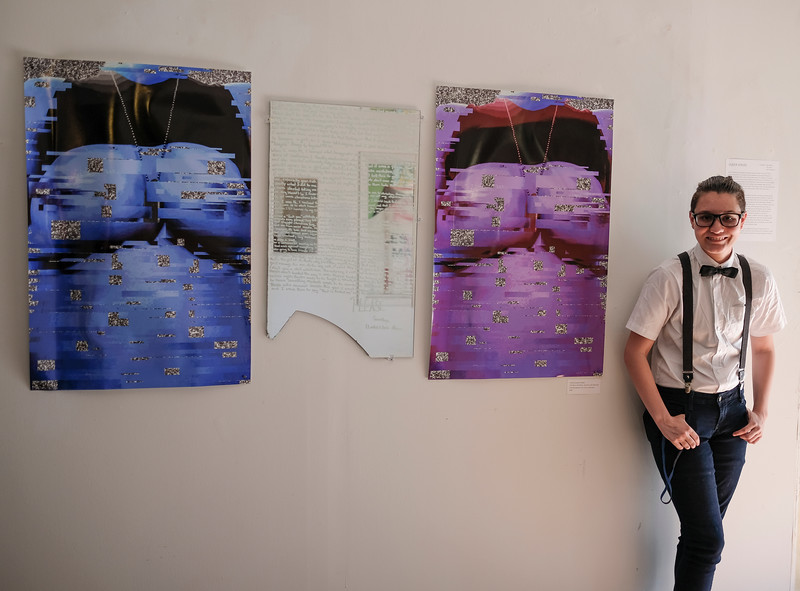 """Tobias Cameran Stalder stands beside his piece titled """"The Boy in the Mirror, the Girl in the Reflection"""".  """"Leelah Alcorn was a 17 year old transgender girl living in Ohio. She killed herself and for a short time it was sensationalized, fetishized, and obsessively documented. Her parents to this day still call her by her birth name in the name of their God. Her suicide letter was the moment I knew I wasn't a girl. What Leelah couldn't put into words was the exact and distinct pain of dysphoria, of knowing you don't quite fit in, of being hated….Using a broken mirror and a paint pen, I transcribed her exact suicide note. While it is read, the person is forced to face themselves, forced to face the missing piece. The viewer is forced into a small window of what it is like to not quite fit in.""""  On either side of the mirror are two prints. """"These are images of myself right before I pull down my binder pixelated through Photoshop to distort the body and create static behind it. I want to invite my viewer in and give them a glimpse of what being transgender is like for me."""""""