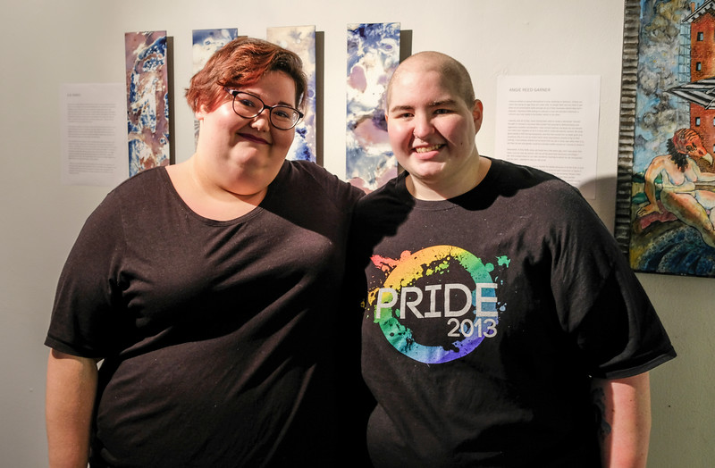 S.N. Parks (left) stands beside their partner MC Lampe (right) at the Queer Voices 2017 art exhibit. Not only is Parks one of the fourteen artists in the exhibit, they are also one of the curators of the show.
