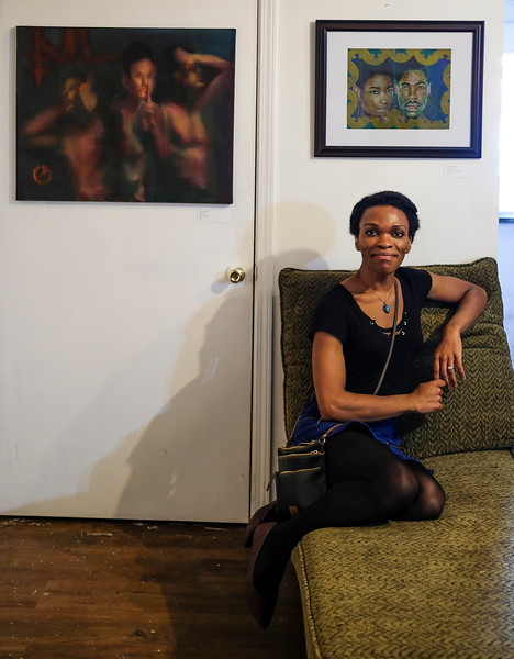 """Jasmine Smith sits below her two pieces titled """"No Evil"""" (left) and """"Bantu Knot"""" (right) at the opening reception of the Queer Voices 2017 art exhibition.  """"After Photographing drag shows and portraits of trans and non binary friends, I have compiled many images of raw individuality. I plan on creating portraits in fantastical worlds while enhancing the figures' gender expression."""""""