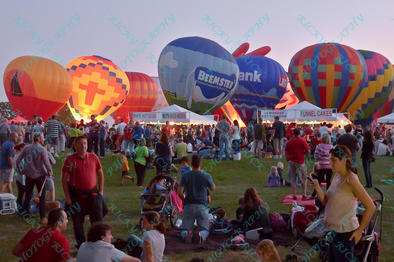 The Beemster and US Bank Hot air balloons alongs with others light up the night sky while crowds gather in the popular event held at Forest Park in St. Louis, MO on 9/19/14
