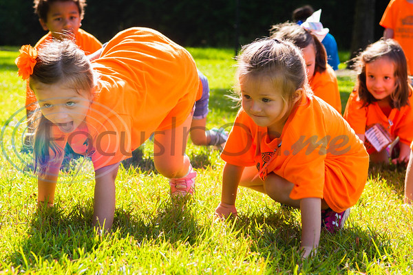 Campers Ryann Paine (left) and Makenna Hasselle run like cheetahs across a field of grass during Zoo Camp Friday at Caldwell Zoo in Tyler.   (Cara Campbell/Tyler Morning Telegraph)