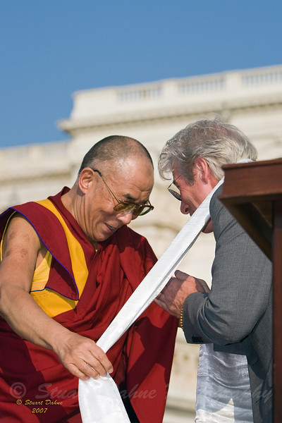 Tibet's exiled spiritual leader the Dalai Lama presents a scarf to actor Richard Gere during a celebration outside the Capitol building after receiving the U.S. Congressional Gold Medal on Capitol Hill in Washington, D.C.