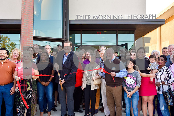 People pose for a ribbon cutting photo during an open house event at the Tyler Morning Telegraph in Tyler, Texas, on Thursday, Oct. 12, 2017. (Chelsea Purgahn/Tyler Morning Telegraph)