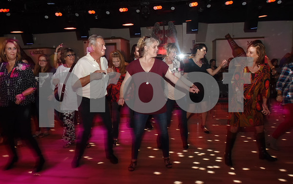 People dance at the Bras for a Cause charity event held at Coach's & Cowboy's bar in Tyler Tuesday Oct. 18, 2016. The event is sponsored by Tyler Women's Council of Realtors as part of National Breast Cancer Awareness Month. Proceeds benefit Susan G. Komen Foundation Tyler Firefighters Care Fund and local fire departments. Firefighters seek bids from the crowd for their themed bras and gift baskets.  (Sarah A. Miller/Tyler Morning Telegraph)