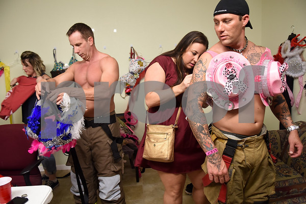 Firefighters Michael Frost of Tyler and Derek Kastning of Winona put on their bras backstage at the Bras for a Cause charity event held at Coach's & Cowboy's bar in Tyler Tuesday Oct. 18, 2016. The event is sponsored by Tyler Women's Council of Realtors as part of National Breast Cancer Awareness Month. Proceeds benefit Susan G. Komen Foundation Tyler Firefighters Care Fund and local fire departments. Firefighters seek bids from the crowd for their themed bras and gift baskets.  (Sarah A. Miller/Tyler Morning Telegraph)