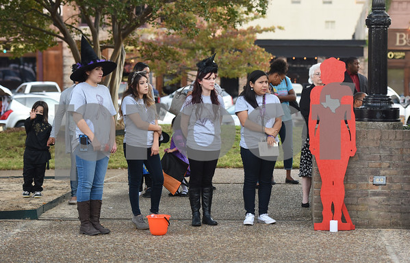 People stand next to a silhouette representing a woman who was killed by domestic violence during the East Texas Crisis Center Domestic Violence Awareness Month Hope Awards held Wednesday night at T.B. Butler Fountain Square.  (Sarah A. Miller/Tyler Morning Telegraph)