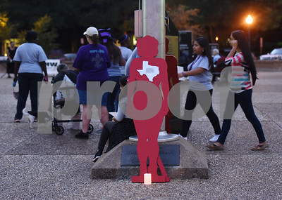 People walk past a silhouette representing a woman who was killed by domestic violence during the East Texas Crisis Center Domestic Violence Awareness Month Hope Awards held Wednesday night at T.B. Butler Fountain Square.  (Sarah A. Miller/Tyler Morning Telegraph)