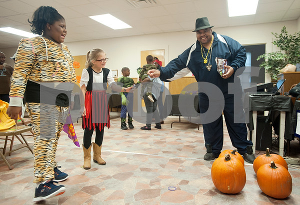 Rev. Erick Bradley gives a Snickers candy bar to Isabella Lorrain, 8, of Bullard, after she played a ring toss game with pumpkins during Harvest Fest at The Cross Baptist Church in Tyler Saturday afternoon. The event featured games and candy for children.  (Sarah A. Miller/Tyler Morning Telegraph)