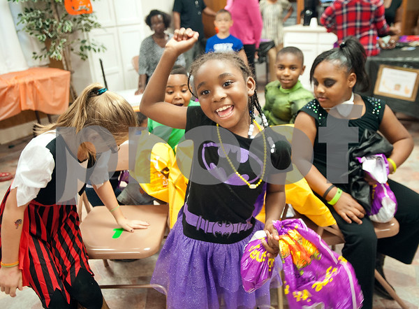 Beinicia Drew, 7, of Tyler, raises her hand after winning a game of musical chairs during Harvest Fest at The Cross Baptist Church in Tyler Saturday afternoon. The event featured games and candy for children.  (Sarah A. Miller/Tyler Morning Telegraph)