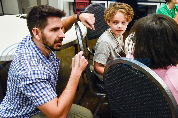 Jesus Sanchez facilitates discussion about coding with Luke Sirianni, 8, and Eden Gentry, 10, during the first Girls Who Code meeting at the Innovation Pipeline in Tyler, Texas, on Wednesday, Oct. 3, 2018. Girls Who Code is a nonprofit organization which aims to support and increase the number of women in computer science. (Chelsea Purgahn/Tyler Morning Telegraph)