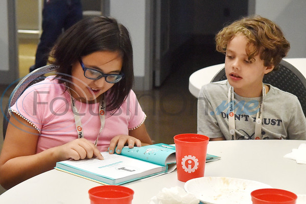 Eden Gentry, 10, reads from the Girls Who Code book as Luke Sirianni, 8, listens during the first Girls Who Code meeting at the Innovation Pipeline in Tyler, Texas, on Wednesday, Oct. 3, 2018. Girls Who Code is a nonprofit organization which aims to support and increase the number of women in computer science. (Chelsea Purgahn/Tyler Morning Telegraph)