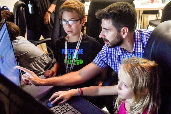 Noah Gentry, 11, left, and Devyn Smith, 8, right, listen as Jesus Sanchez gives them instructions during the first Girls Who Code meeting at the Innovation Pipeline in Tyler, Texas, on Wednesday, Oct. 3, 2018. Girls Who Code is a nonprofit organization which aims to support and increase the number of women in computer science. (Chelsea Purgahn/Tyler Morning Telegraph)