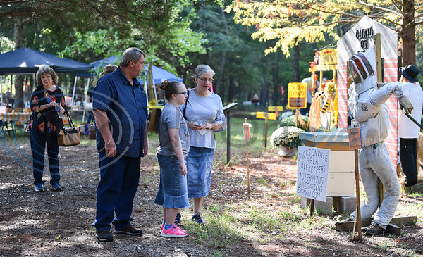 A family walks through the Scarecrow Trail in Jacksonville at Ruth Bowling Nichols Arboretum. Local schools, businesses and other organization decorate scarecrows for the event which will run through Thursday, October 17. (Jessica T. Payne/Tyler Morning Telegraph)