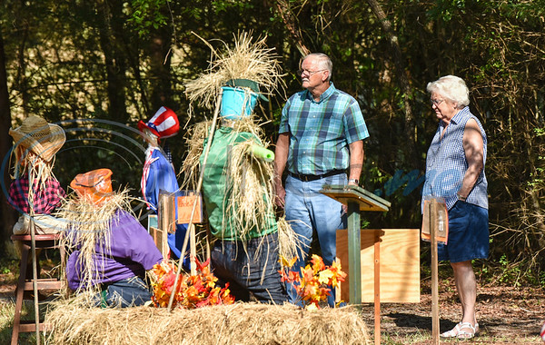 A couple admires scarecrow displays at the Scarecrow Trail in Jacksonville hosted by the Cherokee County Master Gardeners. The event is held at Ruth Bowling Nichols Arboretum and will run from October 5-17. (Jessica T. Payne/Tyler Morning Telegraph)