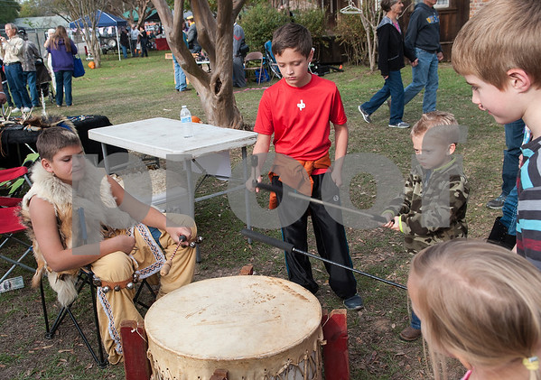 Jared Hill of Longview, part of Tejas Lodge Order of the Arrow, left, plays a Native American style drum with Tristian Claiborne, 10, of Tyler, center, and Marshall Hogue, 4, of Gladewater, at the annual Heritage Syrup Festival Saturday Nov. 14, 2015 in Henderson, Texas. The celebrates the tradition of ribbon cane syrup and features a syrup making demonstration utilizing the Depot Museum's antique mule powered equipment. The festival also features basket weaving,  blacksmithing, folk singers, vendors and square dancing.  (Sarah A. Miller/Tyler Morning Telegraph)