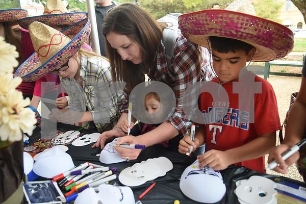 Isaac Hartnauer, 9, of Tyler, at right, decorates a mask during the Dia de los Muertos celebration in downtown Tyler Saturday Nov. 5, 2016.   (Sarah A. Miller/Tyler Morning Telegraph)