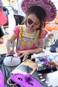 Kelsey Cooper, 6, of Tyler, decorates a mask during the Dia de los Muertos celebration in downtown Tyler Saturday Nov. 5, 2016.   (Sarah A. Miller/Tyler Morning Telegraph)