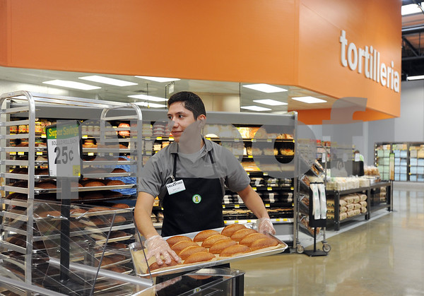 photo by Sarah A. Miller/Tyler Morning Telegraph  Bakery clerk Tino Jaramillo brings out freshly baked bollilo rolls during the grand opening Wednesday morning of the new and expanded Super 1 Foods store at 105 E. Gentry Parkway in Tyler. Pictured behind Jaramillo is the tortilleria that features freshly made flour and corn tortillas.