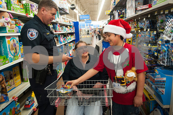 Tyler Police Department officer Mark Lee shops with Rhonda Torxell of Tyler and her son John Trowel, 10,  during the Blue Santa event Thursday Dec. 10, 2015 at Wal-Mart, 5050 Troup Highway in Tyler. Sixty-two children were chosen to participate in the event which paired them with law enforcement officers for a special Christmas shopping trip. The children were able to shop for friends, family members and themselves. The event was organized by The Fraternal Order of Police. More than 100 officers, city employees and family members showed up to help take children shopping with the $4,500 raised for the event.    (Sarah A. Miller/Tyler Morning Telegraph)