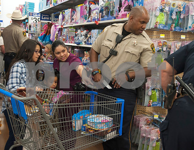 Melanie Munoz, 12, Clarissa Macias, 5, and Katherine Macias shop with Smith County Sheriff's Officer Michael Johnson during the Blue Santa event at Wal-Mart in Tyler Thursday.  (Sarah A. Miller/Tyler Morning Telegraph)