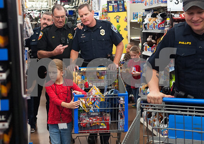Tyler Police Department officers Craig Williams, left, and Wayne Allen, right, shop with Tyler sisters Kora Rucker, 6, and Samantha Rucker, 7,  during the Blue Santa event Thursday Dec. 10, 2015 at Wal-Mart, 5050 Troup Highway in Tyler. Sixty-two children were chosen to participate in the event which paired them with law enforcement officers for a special Christmas shopping trip. The children were able to shop for friends, family members and themselves. The event was organized by The Fraternal Order of Police. More than 100 officers, city employees and family members showed up to help take children shopping with the $4,500 raised for the event.    (Sarah A. Miller/Tyler Morning Telegraph)