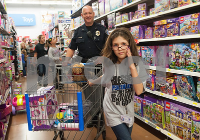 Tyler Police Department officer Chuck Barber shops with Hilary Odle, 9, of Tyler, during the Blue Santa event Thursday Dec. 10, 2015 at Wal-Mart, 5050 Troup Highway in Tyler. Sixty-two children were chosen to participate in the event which paired them with law enforcement officers for a special Christmas shopping trip. The children were able to shop for friends, family members and themselves. The event was organized by The Fraternal Order of Police. More than 100 officers, city employees and family members showed up to help take children shopping with the $4,500 raised for the event.    (Sarah A. Miller/Tyler Morning Telegraph)