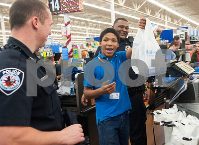 James Hickman, 13, of Tyler, celebrates his purchase of a video game and game controller with Tyler Police Department officers Ty Sorrell, left, and Jeremy Thompson, right, during the Blue Santa event Thursday Dec. 10, 2015 at Wal-Mart, 5050 Troup Highway in Tyler. Sixty-two children were chosen to participate in the event which paired them with law enforcement officers for a special Christmas shopping trip. The children were able to shop for friends, family members and themselves. The event was organized by The Fraternal Order of Police. More than 100 officers, city employees and family members showed up to help take children shopping with the $4,500 raised for the event.    (Sarah A. Miller/Tyler Morning Telegraph)