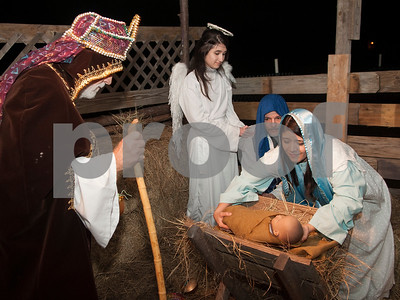 Wiseman Farrell Barnard and angel Hopie Snyder stand over Ron Sexton as Joseph and Leslie Sexton as Mary and as they depict the manger scene of Jesus' birth at West Lake Baptist Church in Chandler Wednesday Dec. 9, 2015 during rehearsal for Night in Bethlehem. Night in Bethlehem is a live reenactment depicting the city of Bethlehem the night of our Jesus' birth.   (Sarah A. Miller/Tyler Morning Telegraph)
