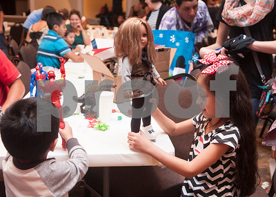 Siblings Jayden Lopez, 3, and Aubrey Lopez, 7, play with their newly unwrapped presents after a special Christmas dinner and gift event for Jackson Elementary School students at Friendly Baptist Church in Tyler Dec. 11, 2015. Students from the church's youth group raised the money for the event which benefitted 45 children from Jackson Elementary. Youth group members also cooked the meal. Jackson Elementary students were nominated by their teachers and school counselors to attend the event.   (Sarah A. Miller/Tyler Morning Telegraph)