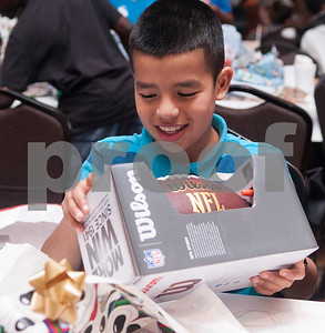 Martin Briones, 11, unwraps a football during a special Christmas dinner and gift event for Jackson Elementary School students at Friendly Baptist Church in Tyler Dec. 11, 2015. Students from the church's youth group raised the money for the event which benefitted 45 children from Jackson Elementary. Youth group members also cooked the meal. Jackson Elementary students were nominated by their teachers and school counselors to attend the event.   (Sarah A. Miller/Tyler Morning Telegraph)