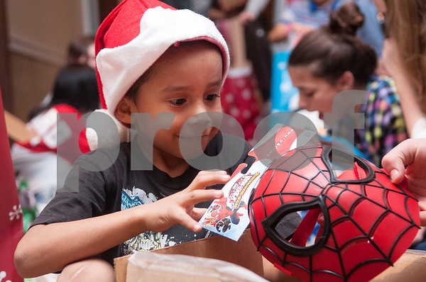 Pedro Avila, 6, unwraps a Spiderman mask during a special Christmas dinner and gift event for Jackson Elementary School students at Friendly Baptist Church in Tyler Dec. 11, 2015. Students from the church's youth group raised the money for the event which benefitted 45 children from Jackson Elementary. Youth group members also cooked the meal. Jackson Elementary students were nominated by their teachers and school counselors to attend the event.   (Sarah A. Miller/Tyler Morning Telegraph)