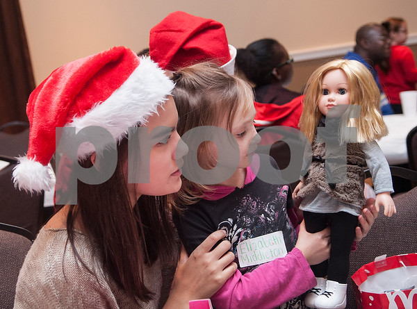 Destiny Tucker, 15, watches Elizabeth Middleton, 6, enjoy her new doll she just unwrapped during a special Christmas dinner and gift event for Jackson Elementary School students at Friendly Baptist Church in Tyler Dec. 11, 2015. Students from the church's youth group raised the money for the event which benefitted 45 children from Jackson Elementary. Youth group members also cooked the meal. Jackson Elementary students were nominated by their teachers and school counselors to attend the event.   (Sarah A. Miller/Tyler Morning Telegraph)