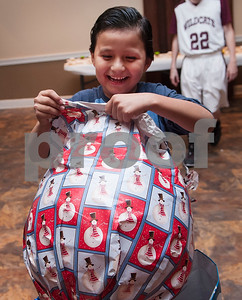 Christopher Torres, 9, unwraps a large ball during a special Christmas dinner and gift event for Jackson Elementary School students at Friendly Baptist Church in Tyler Dec. 11, 2015. Students from the church's youth group raised the money for the event which benefitted 45 children from Jackson Elementary. Youth group members also cooked the meal. Jackson Elementary students were nominated by their teachers and school counselors to attend the event.   (Sarah A. Miller/Tyler Morning Telegraph)
