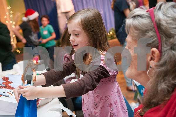 Nannette Kirton watches her granddaughter Aizlynn Middleton, 5, play with a new doll during a special Christmas dinner and gift event for Jackson Elementary School students at Friendly Baptist Church in Tyler Dec. 11, 2015. Students from the church's youth group raised the money for the event which benefitted 45 children from Jackson Elementary. Youth group members also cooked the meal. Jackson Elementary students were nominated by their teachers and school counselors to attend the event.   (Sarah A. Miller/Tyler Morning Telegraph)