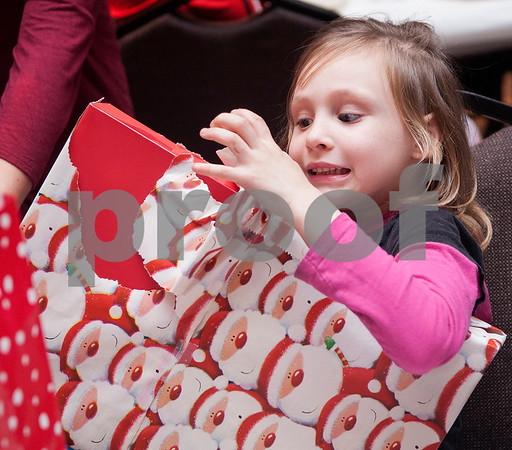 Elizabeth Middleton, 6, unwraps a present during a special Christmas dinner and gift event for Jackson Elementary School students at Friendly Baptist Church in Tyler Dec. 11, 2015. Students from the church's youth group raised the money for the event which benefitted 45 children from Jackson Elementary. Youth group members also cooked the meal. Jackson Elementary students were nominated by their teachers and school counselors to attend the event.   (Sarah A. Miller/Tyler Morning Telegraph)