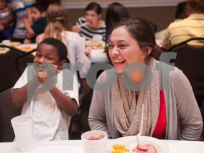 Jaden Allen, 7, eats with Ashlinn Vega, 15, during a special Christmas dinner and gift event for Jackson Elementary School students at Friendly Baptist Church in Tyler Dec. 11, 2015. Students from the church's youth group raised the money for the event which benefitted 45 children from Jackson Elementary. Youth group members also cooked the meal. Jackson Elementary students were nominated by their teachers and school counselors to attend the event.   (Sarah A. Miller/Tyler Morning Telegraph)