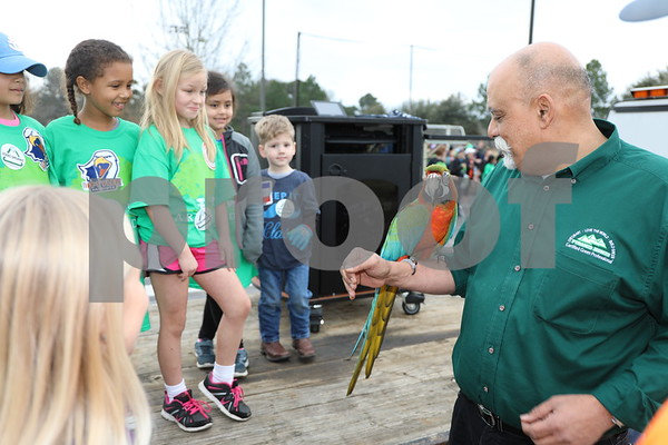 Anwar Khalifa, president of Pyramid Homes, shows his pet macaw to children durning the Tyler Arbor Day Event at UT Tyler