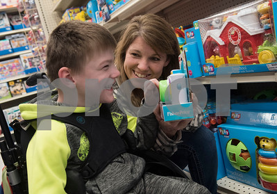 Christi Penning shows David Wurtz, 4, an interactive camera toy as he shops at Big Lots in the French Quarter Shopping Center in Tyler on Friday Dec. 8, 2017. Over 50 East Texas students with visually impairments were given money to purchase a gift to donate to Toys for Tots during their Annual Christmas Outing and Shopping Event.  (Sarah A. Miller/Tyler Morning Telegraph)