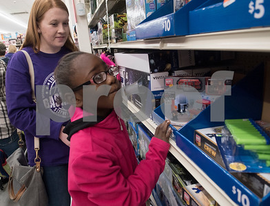 Madison Hudsucker assists Neisha Jackson, 8, as she shops at Big Lots in the French Quarter Shopping Center in Tyler on Friday Dec. 8, 2017. Over 50 East Texas students with visually impairments were given money to purchase a gift to donate to Toys for Tots during their Annual Christmas Outing and Shopping Event.  (Sarah A. Miller/Tyler Morning Telegraph)