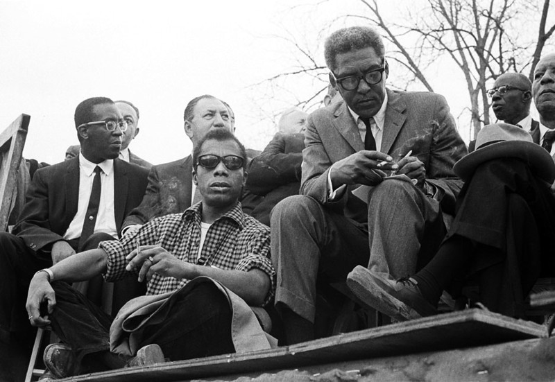 Front left: James Baldwin, author, with cigarette<br /> Front center: Bayard Rustin, march coordinator, with cigarette and writing<br /> Front right: A. Philip Randolph, President of the Brotherhood of Sleeping Car Porters<br /> Selma to Montgomery, Alabama Civil Rights March; March 25, 1965<br />     - Photo by Stephen Somerstein©