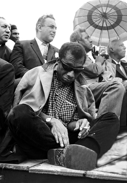 Front: James Baldwin looking at sole of shoe, author,  overcoat over shoulders<br /> Rear right of Baldwin: Bayard Rustin<br /> Rear left of Baldwin: Union leader<br /> Rear right: A. Philip Randolph, Brotherhood of Sleeping Car Porters<br /> Selma to Montgomery, Alabama Civil Rights March; March 25, 1965<br />     - Photo by Stephen Somerstein©