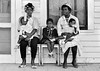 Two mothers with children watching marchers on porch<br /> <br /> Selma to Montgomery, Alabama Civil Rights March; March 23-25, 1965