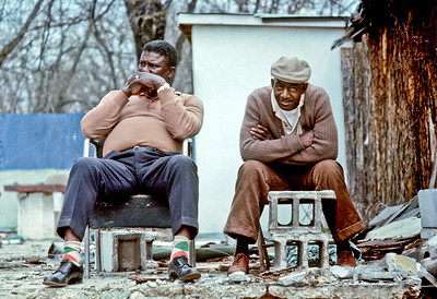 Selma to Montgomery, Alabama Civil Rights March; March 24-26, 1965: Two negro men seated on cement blocks, while watching marchers. {COLOR}