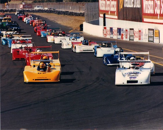 """Entrance to turn 11 before the start of the race at Sears Point, CA. Believed to be a National race with many CSR entries paid for by Tom Foster and Chuck Billington to bolster the average entries to help CSR maintain national class status. The field was paced by a former H Modified car. Many DSR started as CSR cars then pitted after the first lap to allow the """"real"""" CSR racers to run their race.<br /> <br /> Maybe 22 sports racers can be picked out in the photo?"""