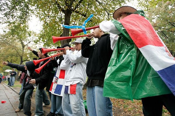 Red Sox fans draped with Domnican Republic flags show their support during a World Series parade in Boston, Saturday, October 30, 2004.  The Red Sox swept the St. Louis Cardinals to win their first World Series in 84 years.