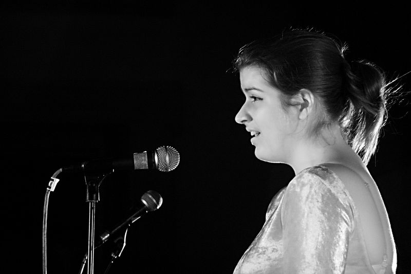 A headshot of Becky singing