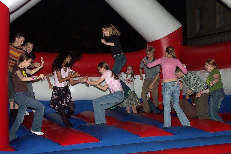 People having fun on the bouncy castle outside